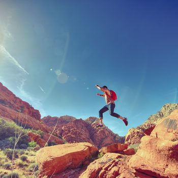 man jumping from one rock formation to another in the desert